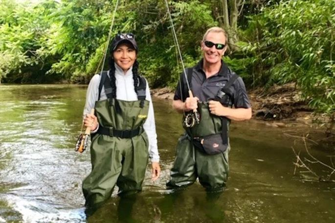 Robson and Zoila standing in a river wearing waterproof waders and holding fishing rods