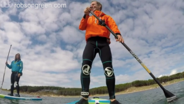 Robson Green is paddle-boarding on the Welsh Isle of Anglesey.