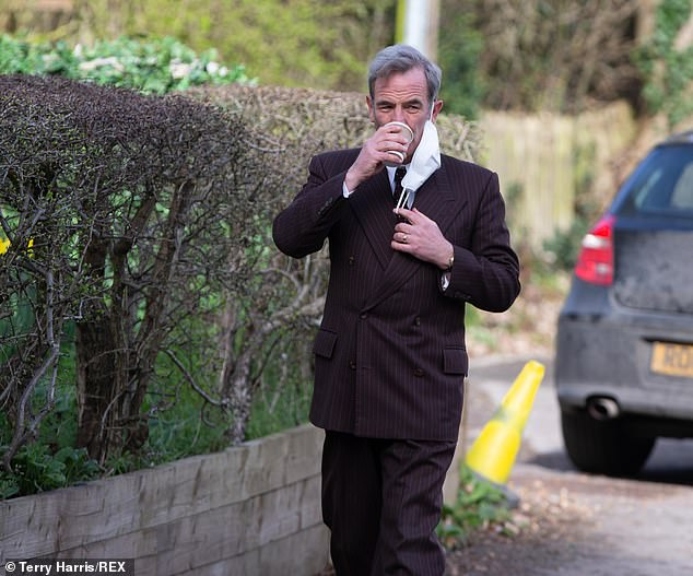 Taking a break: Robson Green was seen removing his face covering so as to enjoy a sip of coffee on the set of Grantchester in Cambridge on Thursday