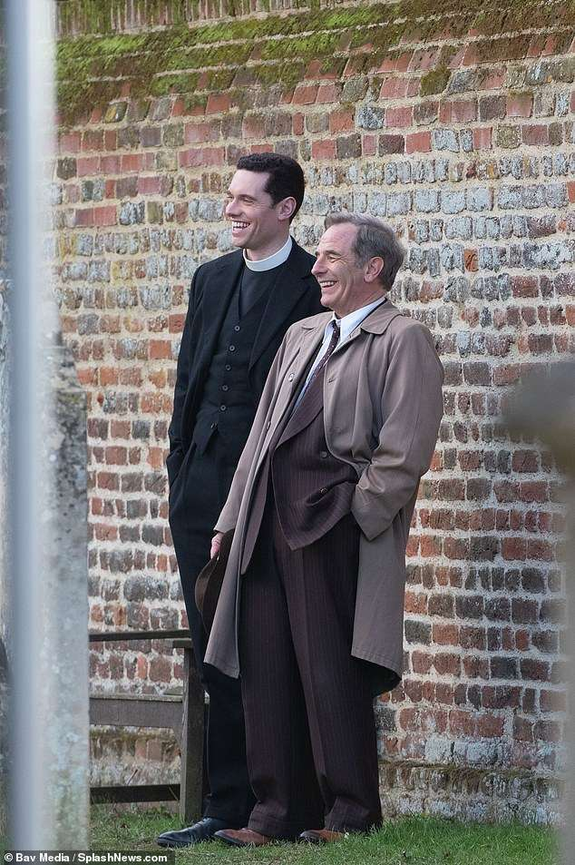 Pals: Tom, who plays Reverend William Davenport, wore his usual vicar ensemble, posing alongside Robson in front of a stony wall